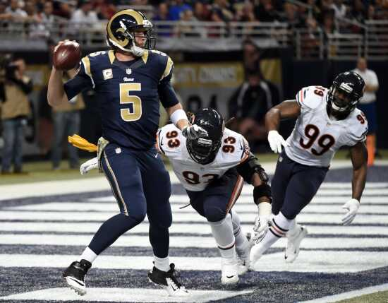 be5c92ca8ab Rams quarterback Nick Foles scrambles in his own end zone while being  pressured by the Bears  Will Sutton (93) and Lamarr Houston during the  second quarter ...